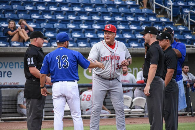 Chattanooga Lookouts manager Pat Kelly, who spent three seasons in Pensacola, exchanges lineup cards with Blue Wahoos manager Ramon Borrego.