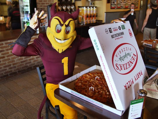Sun Devil mascot Sparky opens up a box of Venezia's Pizzeria's pizza. The pizzeria will offer giant slices at ASU games starting this year.