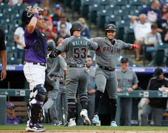 Colorado Rockies catcher Dom Nunez, front, looks on as Arizona Diamondbacks' Christian Walker, center, celebrates his two-run home run with Ketel Marte in the first inning of a baseball game Tuesday, Aug. 13, 2019, in Denver. (AP Photo/David Zalubowski)
