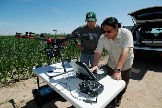 In this Thursday, July 11, 2019, photograph, United States Department of Agriculture intern Alex Olsen, left, and engineering technician Kevin Yemoto work to set up a drone for flight over a research farm northeast of Greeley, Colo.