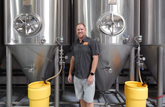 Jeff Huss stands in front of two of the four tanks that started it all six years ago at Huss Brewing.