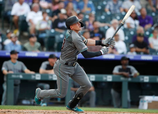 Arizona Diamondbacks' Nick Ahmed follows the flight of his two-run home run off Colorado Rockies starting pitcher Jeff Hoffman in the first inning of a baseball game Tuesday, Aug. 13, 2019, in Denver. (AP Photo/David Zalubowski)