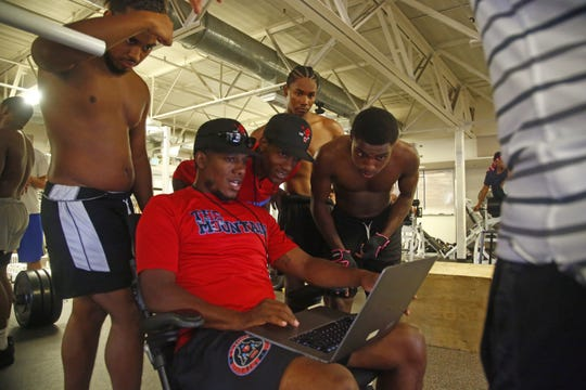 South Mountain's head coaches' Marcus Carter (center) and Mark Carter look over max sheets with Xavier Palmer (L) as the team works out before practice at South Mountain High School in Phoenix, Ariz. on August 5, 2019.