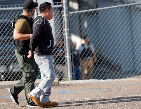 Un agente de ICE guía a un hombre arrestado, durante redada a planta de alimentos en Mississippi.