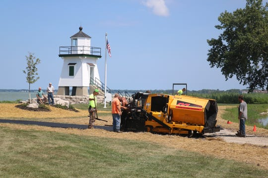 Crews continue work Wednesday to finish the landscaping project around the Port Clinton Lighthouse and Derby Pond in time for this weekend's festival.