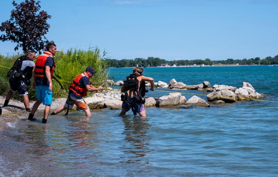 Port Huron firefighters serving as rope tenders work to pull a diver back to shore during a dive rescue training session Wednesday, Aug. 14, 2019.
