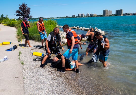 The Port Huron Fire Department runs a training scenario Wednesday, Aug. 14, 2019, along the Blue Water River Walk in Port Huron. The department is working to get their Public Safety Diver certifications, which will let them establish an underwater rescue team.