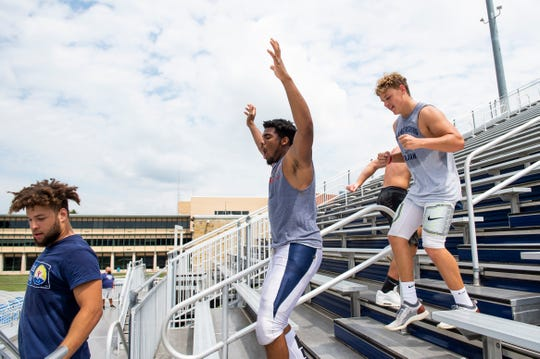 Terrell Williams, center, pumps up his teammates as they run stairs during a Chambersburg football practice at Trojan Stadium on Wednesday, August 14, 2019.