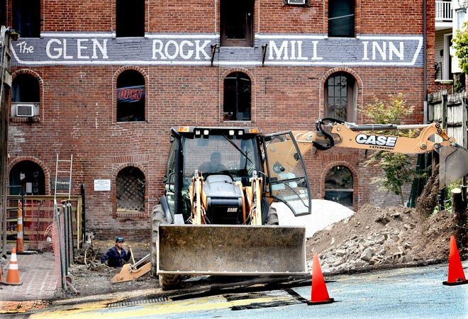 Victor Cruz, left, and a crew from 1st Impression Stormwater and Excavating, Parkton, Maryland, works at the Glen Rock Mill Inn Wednesday, Aug. 14, 2019. The landmark restaurant and Glen Rock Borough are working to replace aging storm water drains which run beneath the inn's patio area. Inn owner Brandon Hufnagel said he plans to have the outdoor seating area renovated and open by the spring of 2020. Bill Kalina photo