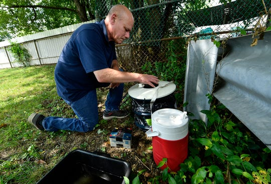 Lee Graybill, program administrator of the Mosquito Surveillance Program in York County, places mosquito traps at a location off of Roosevelt Avenue in York, Wednesday, August 14, 2019. Captured mosquitoes will be tested for West Nile Virus. John A. Pavoncello photo