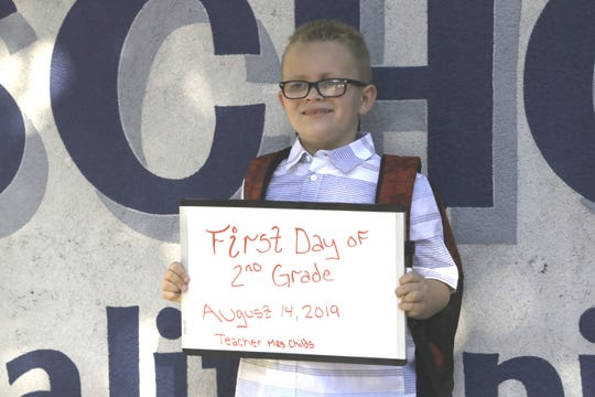 Jonathan Jones, 7, poses as his parents take a first-day-of-school photo in front of Turtle Bay School in Redding on Wednesday, Aug. 14, 2019.