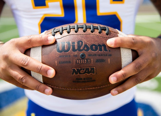 SDSU running back Mikey Daniel holds a football while posing for a portrait at Dana J. Dykhouse Stadium, Tuesday, Aug. 13.
