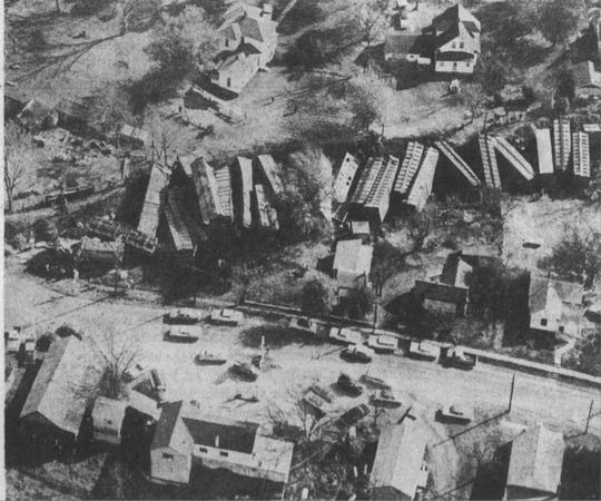 "Here is the original 1962 photo caption: ""BIG JUMBLE  Between 30 and 32 cars of a northbound Frisco freight train left the Kansas City main line at 9 a.m. today in a cut just south of the Ash Grove Main Street. After the dust cleared, residents in trackside homes saw this nightmarish jumble of stacked cars faced by wrecker crews from Springfield. No one was hurt, although this picture shows how close cars caem to some houses. You're looking east here, with Highway F in the foreground."""