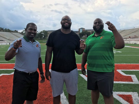 Newly-signed right tackle Calvin Ashley officially enrolled at FAMU on Wednesday, Aug. 14, 2019. He will be a major part in the offense for head coach Willie Simmons (left) and offensive line coach Alex Jackson.