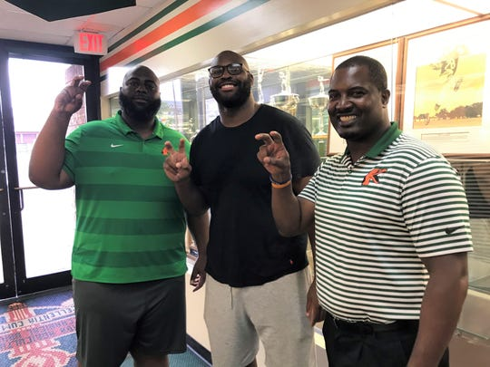 Right tackle Calvin Johnson poses in front of some of the hardware inside the Galimore-Powell Field House at FAMU on Wednesday, Aug. 14, 2019. He shared this moment with offensive line coach Alex Jackson (left) and head coach Willie Simmons.