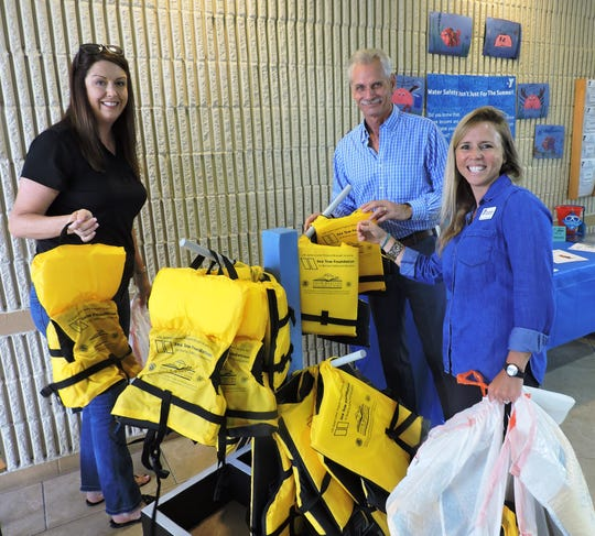 Jennifer Ahern, Manager of Outreach and Communications for Children's Services Council of Martin County, Dave Heaton, Executive Director of Children's Services Council of Martin County and Elisha Stoecklin, Executive Director of the YMCA of Martin County Richard C. Geisinger, Sr. Branch, assemble the Life Jacket Loaner Station.