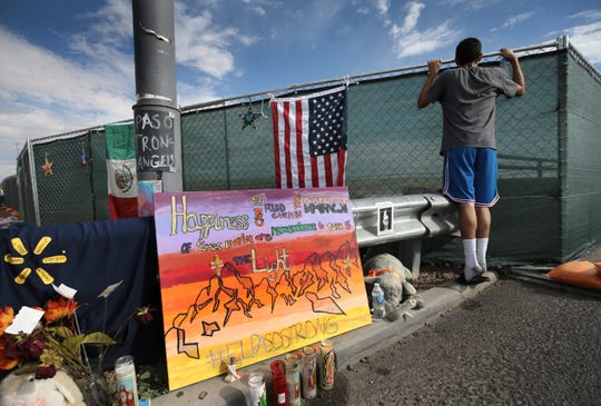 George Encerrado peeks over the fence at the Walmart below as he visits the makeshift memorial where 22 people were murdered on August, 3. El Pasoans are still visiting and adding to the memorial in droves nine day after the incident.