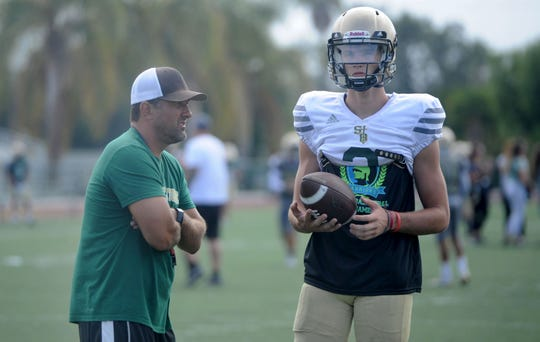 Head coach Tony Henney talks with  starting quarterback Gavin Beerup during St. Bonaventure's practice on Tuesday. The Seraphs have big expectations for the 2019 season.