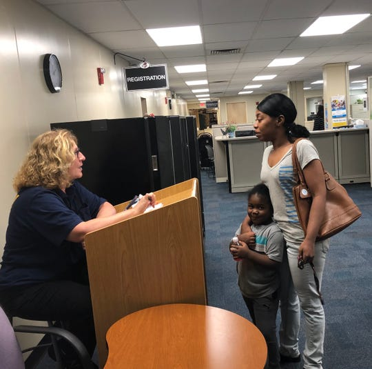Antonio Powers smiles as his mother, Geneva Powers, talks with school district security officer Pana Papamihalakis. Powers was at the  Vineland Public School Administration Building to register her children for the  2019-20 school year.