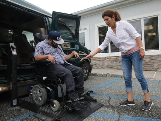 Oliver Hilario gets help from his mom, Sonia Hilario, who is his caregiver get into the van at Bridges in New City Aug. 13, 2019.