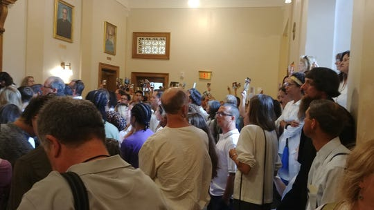 Families gathered in the lobby outside the courtroom holding pictures of their families as oral arguments were heard in the case to reinstate religious exemptions for vaccinations.