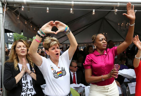 Barbara Poma, from left, owner of Pulse nightclub, and city commissioners Patty Sheehan and Regina Hill react during a public remembrance ceremony June 12, 2017, for shooting victims at Pulse nightclub in Orlando, Fla.