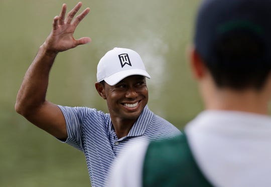 Tiger Woods smiles as he greets fans on the 14th hole during the pro-am at the BMW Championship.