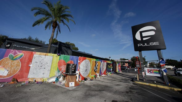 FILE - In this Nov. 30, 2016 file photo, artwork and signatures cover a fence around the Pulse nightclub, scene of a mass shooting, in Orlando, Fla.  Jurors in the federal trial of  Noor Salman,  the Pulse nightclub gunman's widow, have gotten a look inside his Florida condo through crime scene photos taken as FBI agents searched the home. They also saw some of her husband Omar Mateen's web browsing history Tuesday, March 20, 2018, including beheading videos created by the Islamic State group Mateen had pledged allegiance to. Salman is accused of aiding and abetting her husband in the 2016 attack that left 49 people dead.