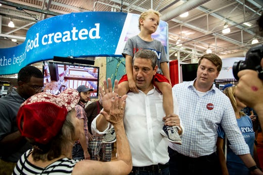 Rep. Tim Ryan, D-OH, with his son Brady on his shoulders, high-fives a visitor of the Iowa State Fair on Aug. 10, 2019, in Des Moines, Iowa. Ryan announced he was seeking the 2020 Democratic nomination on April 4, 2019.