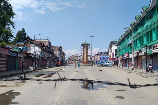In this Thursday, Aug. 8, 2019 file photo, Kashmiri women walk at a deserted Lal Chowk square, a frequent site for anti-India protests, in Srinagar, Indian controlled Kashmir.