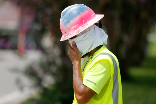 Construction worker Dineose Vargas wipes his face at a construction site on the Duncan Canal in Kenner, Louisiana, Tuesday, Aug. 13, 2019.