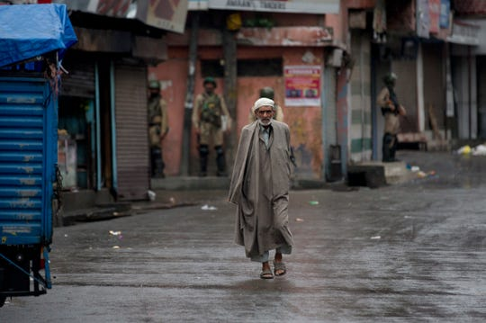 A Kashmiri man walks as Indian paramilitary soldiers stand guard during security lockdown in Srinagar on Aug. 14, 2019.