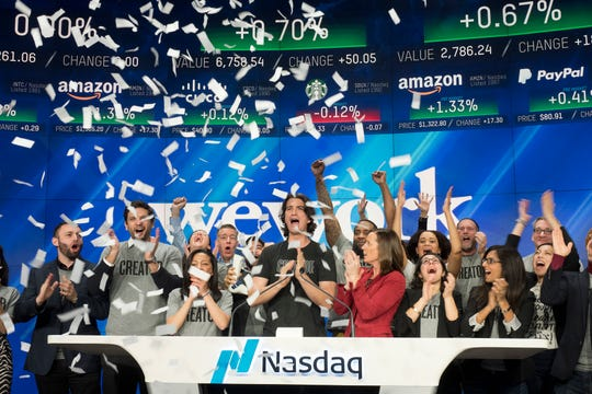 In this Jan. 16, 2018 file photo, Adam Neumann, center, co-founder and CEO of WeWork, attends the opening bell ceremony at Nasdaq in New York.
