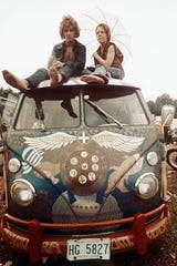 Concert-goers sit on the roof of a Volkswagen bus at the Woodstock Music and Arts Fair at Bethel, N.Y., in mid-August 1969. The three-day concert attracted hundreds of thousands of people, and became a landmark cultural event of the late '60s. (AP Photo) ORG XMIT: APHS200 [Via MerlinFTP Drop]