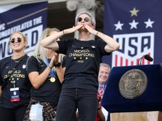 U.S. women national soccer team forward Megan Rapinoe, center, blows a kiss to the crowd at New York City Hall after the ticker-tape parade for the team's World Cup championship parade.