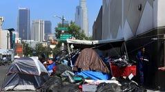 Belongings of the homeless crowd a downtown Los Angeles sidewalk in Skid Row.