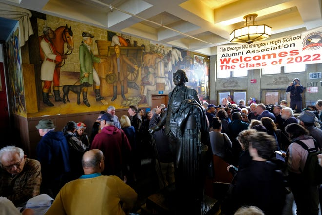 """In this Aug. 1, 2019, file photo, people fill the main entryway of George Washington High School to view the controversial 13-panel, 1,600-square foot mural, the """"Life of Washington,"""" during an open house for the public in San Francisco."""
