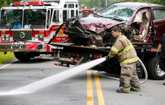 A Parkertown firefighter hoses down Parkertown Drive in Little Egg Harbor Township early Thursday afternoon, August 15, 2019, at the scene of a single car fatal accident earlier in the day.
