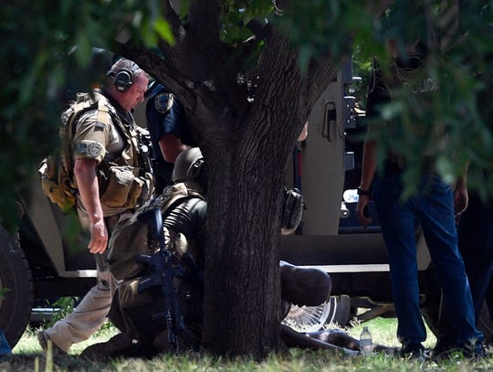 A suspect with his head down is treated after capture Thursday by members of the Abilene SWAT team on Kirkwood Street.