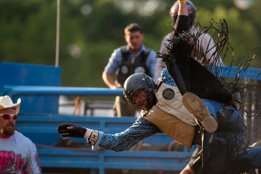 Cowboy Hayden Townsend falls from a bull during a Lost Nations Rodeo on Wednesday, Aug. 14, 2019 at the Calhoun County fairgrounds in Marshall, Mich.