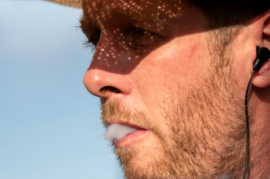 Cowboy Jake McLaughlin smokes a cigarette before competing in the Lost Nations Rodeo on Wednesday, Aug. 14, 2019 at the Calhoun County fairgrounds in Marshall, Mich.