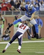 Detroit Lions tight end Tony Scheffler (85) jumps over Houston Texans defensive back Brice McCain (21) during overtime of an NFL football game at Ford Field in Detroit, Thursday, Nov. 22, 2012.