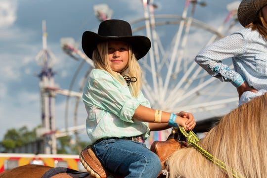 Cowgirl Madison Raak, 7, rides in the Lost Nations Rodeo on Wednesday, Aug. 14, 2019 at the Calhoun County fairgrounds in Marshall, Mich.