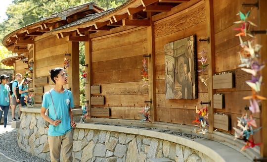 "Tyler Veu, 16, of Bothell, walks along the Bainbridge Island Japanese American Exclusion Memorial while visiting the site with the ""In My Backyard"" youth leadership and conservation development program on Thursday. The program was created by a ranger with the National Park Service from South Kitsap."