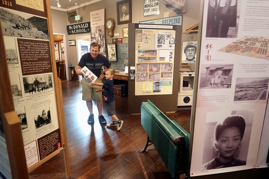 Bainbridge Historical Museum volunteer Sean Megy helps Camden Marshall, 5, with a scavenger hunt sheet on Thursday. Camden and his family were visiting the museum from Texas.