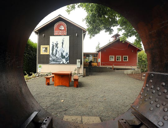 The Bainbridge Island Historical Museum buildings are framed by the partial creosote retort that is on display in the yard on Thursday.