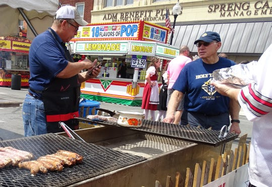 Mark Fox grills up some bratwurst at the Knights of Columbus tent on South Sandusky Avenue as the Bucyrus Bratwurst Festival gets started on Thursday.