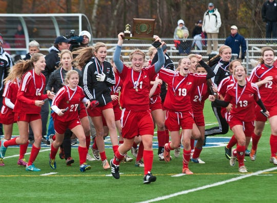CVU's Taylor Goldsborough (center) and her teammates celebrate their victory over Essex in the Division 1 state championship game in Burlington on Saturday, November 3, 2012.