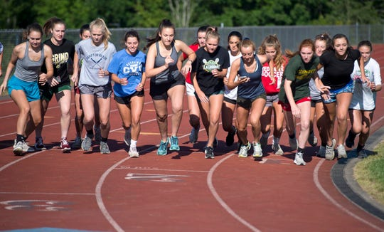 Champlain Valley girls soccer players line up to run a mile for a fitness test during the team's first preseason practice in Hinesburg on Thursday, Aug. 15, 2019.