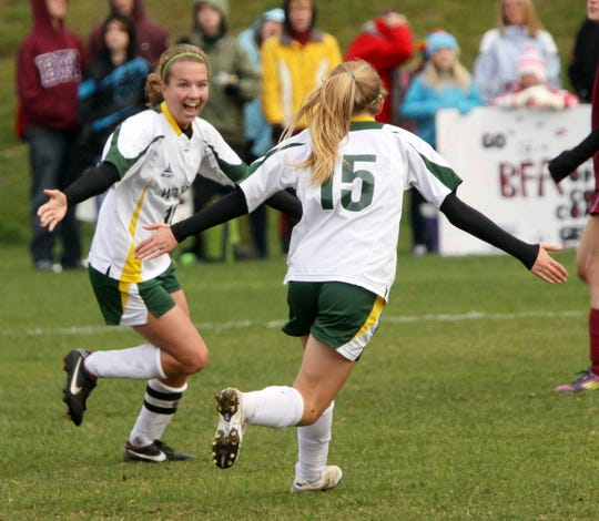 Peoples Academy's Katie Stames, left, and Hannah Merriam, right, celebrate one of Stames' four goals in the Wolves' 9-0 win in the Division III girls soccer high school state championship game Saturday at Williamstown High School.